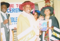 Graduating Don Bishop Samson Kitheka from UK (Centre) president world Federation of Churches presenting gifts to Pastor Shirley Rose from Tanzania (R). Pastor Joseph Kiyimba with microphone interpreting